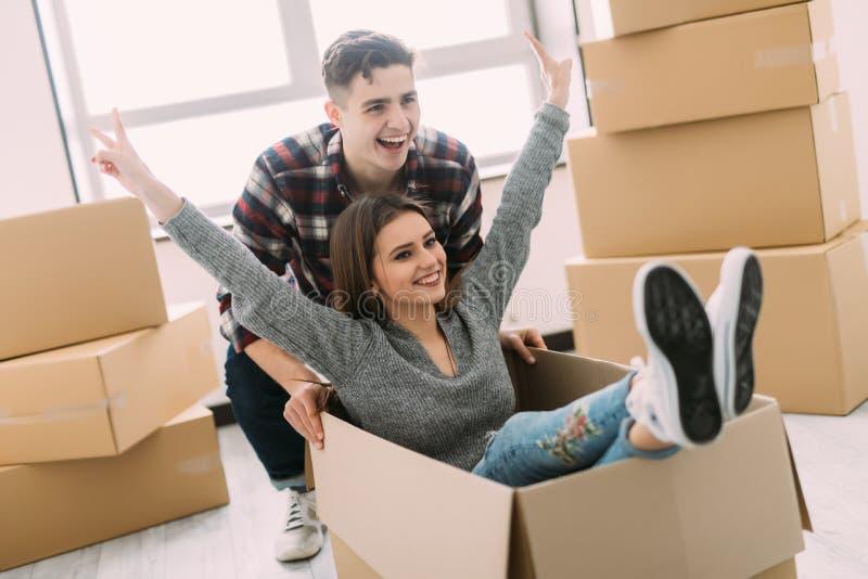 Hem-, folk-, flyttning- och fastighetbegrepp - lyckligt par som har gyckel och rider i kartonger på det nya hemmet arkivfoto