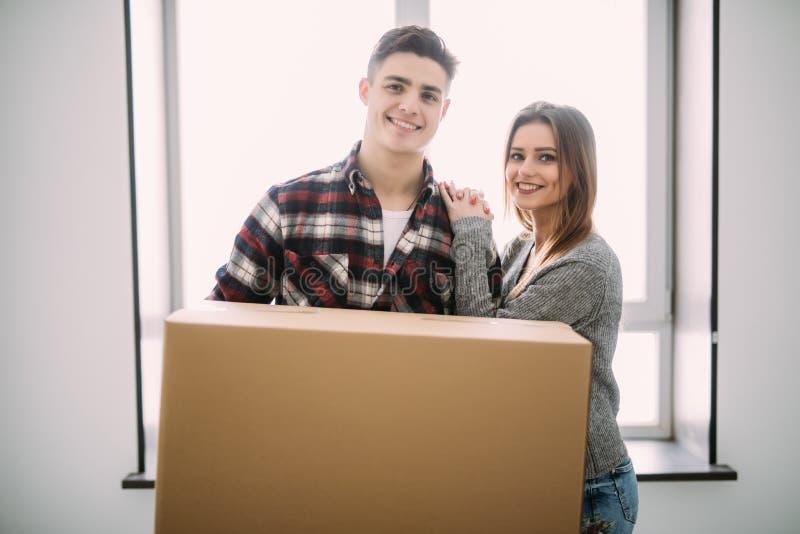 Hem-, folk-, reparations- och fastighetbegrepp - le par med stora kartonger som flyttar sig till det nya stället arkivbild