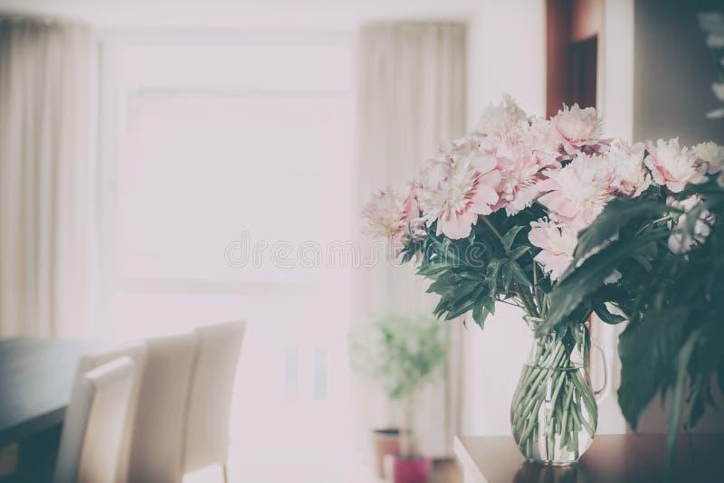 Hem- garnering med nya rosa pioner samlar ihop i den glass vasen på vardagsrumbakgrund, den retro nostalgiker royaltyfri fotografi