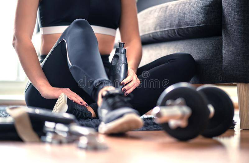 Hem- genomkörare, viktutbildning och konditionövningsbegrepp Kvinna i sportswearen som sitter i vardagsrum med idrottshallutrustn royaltyfri foto