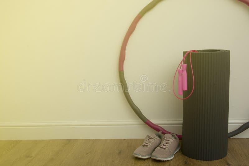 Hem- genomkörarebegrepp Kondition yoga, sportutrustning - matt yoga, överhopprep, sportskor och hulabeslag - ett stort beslag rot royaltyfria foton