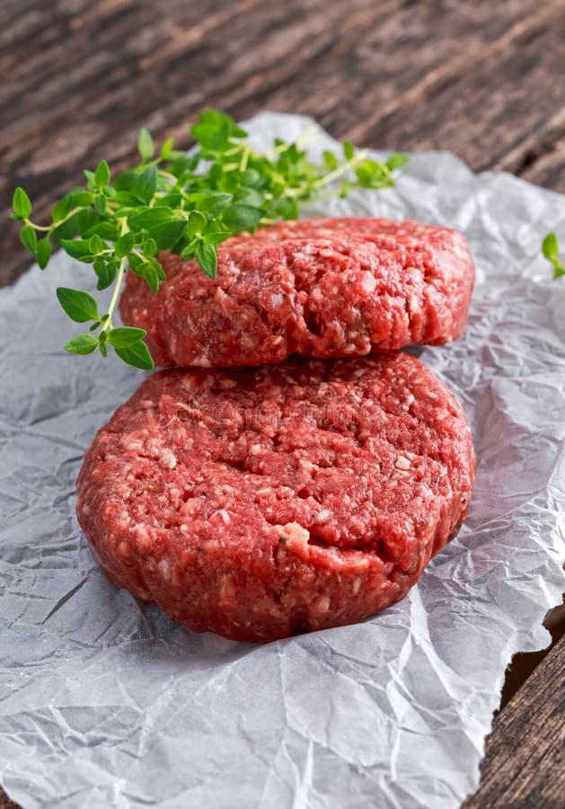 Hem- handgjorda rå finhackade hamburgare för nötköttbiff på scrumbled papper royaltyfri bild