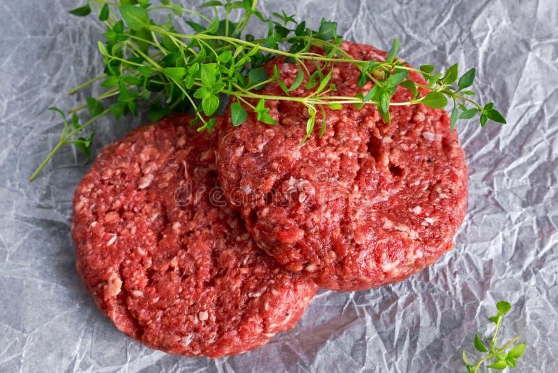 Hem- handgjorda rå finhackade hamburgare för nötköttbiff på scrumbled papper arkivfoton