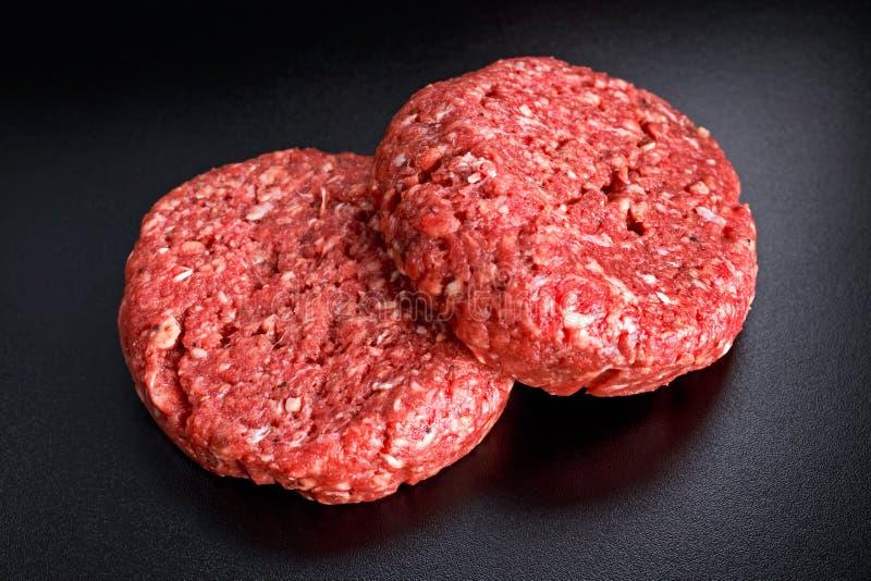 Hem- handgjorda rå finhackade hamburgare för nötköttbiff på svart bräde royaltyfria bilder