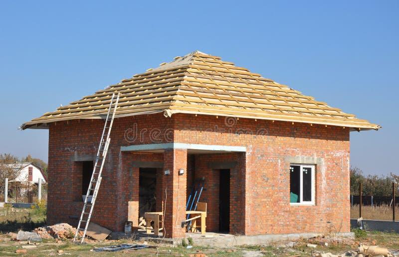 Hem- inrama för ny konstruktion för takmembranbeläggningar trämed taktaksparrar och metallstegen som är utomhus- mot en blå himme arkivfoton