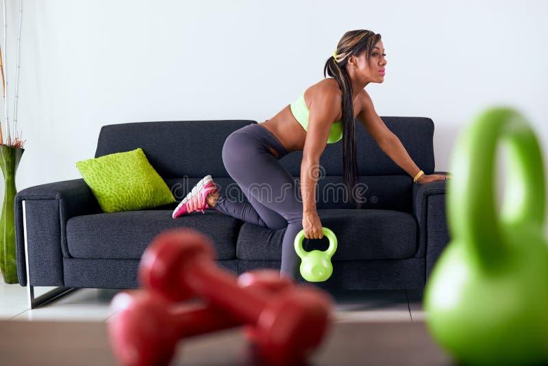 Hem- konditionsvart kvinnautbildning med vikter på soffan arkivbilder