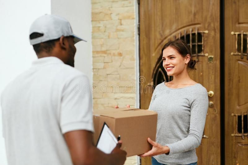 Hem- leverans KurirDelivering Package To klient royaltyfria foton