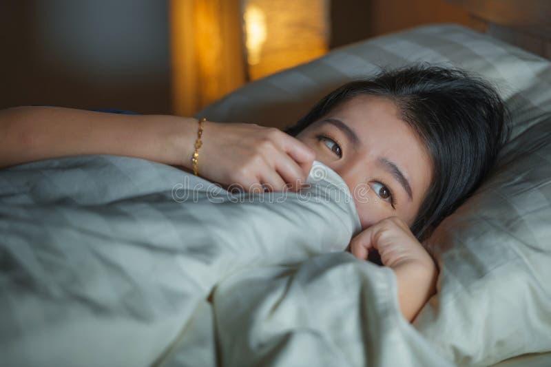 Hem- livsstilstående av den unga härliga ledsna och deprimerade asiatiska kinesiska kvinnan som är vaken i natten för säng som se fotografering för bildbyråer