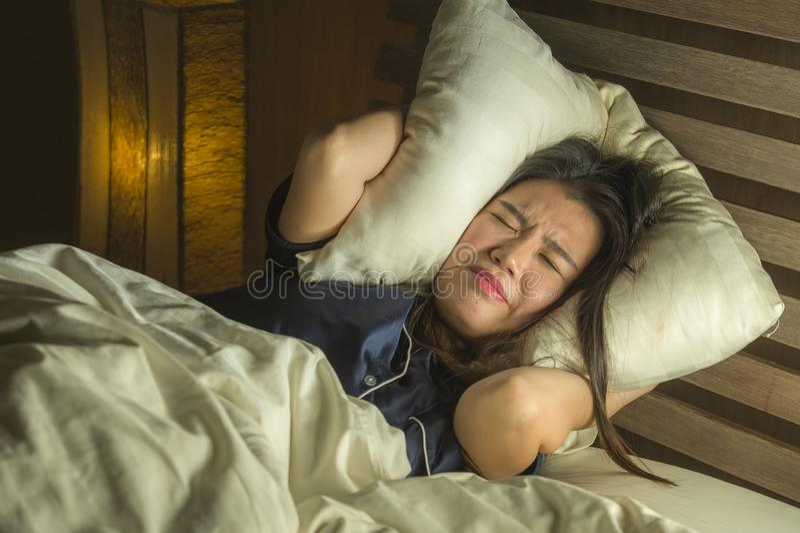 Hem- livsstilstående av den unga härliga ledsna och deprimerade asiatiska koreanska kvinnan som är vaken i natten för säng som se arkivbilder