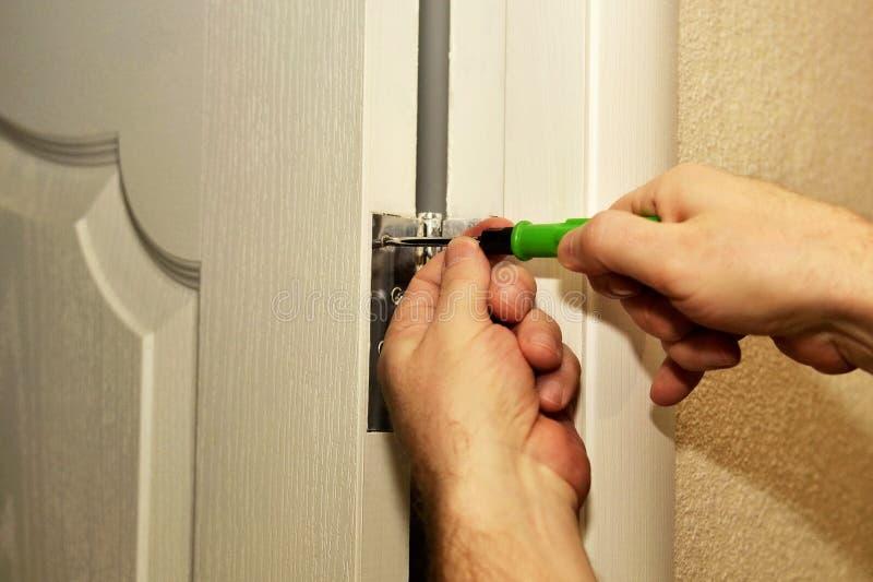 Hem- reparation, installation av dörrgångjärn royaltyfria foton