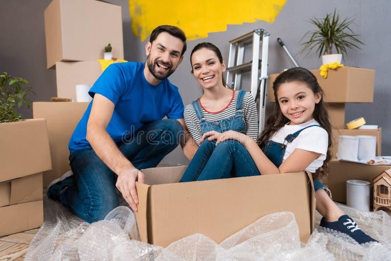 Hem- reparation Rörande ung familj till den nya lägenheten Reparation i det till salu huset royaltyfria foton