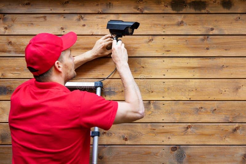 Hem- säkerhet - man som installerar den utomhus- bevakningkameran på träväggkopieringsutrymme royaltyfri foto