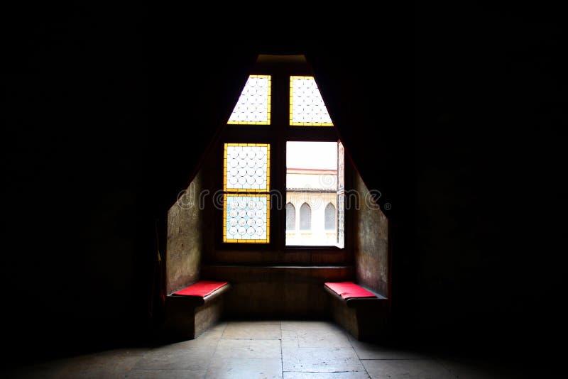 Hem- sötsakhem: Fönster med bänken i en mörk miljö royaltyfri foto