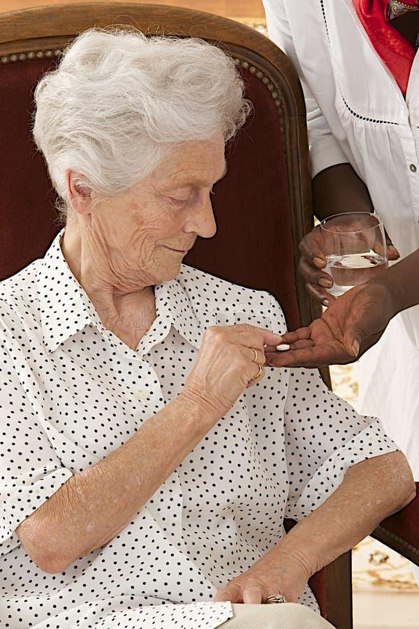 Hem- sjuksköterska som hemma ger äldre kvinnavitaminpreventivpillerar royaltyfri fotografi
