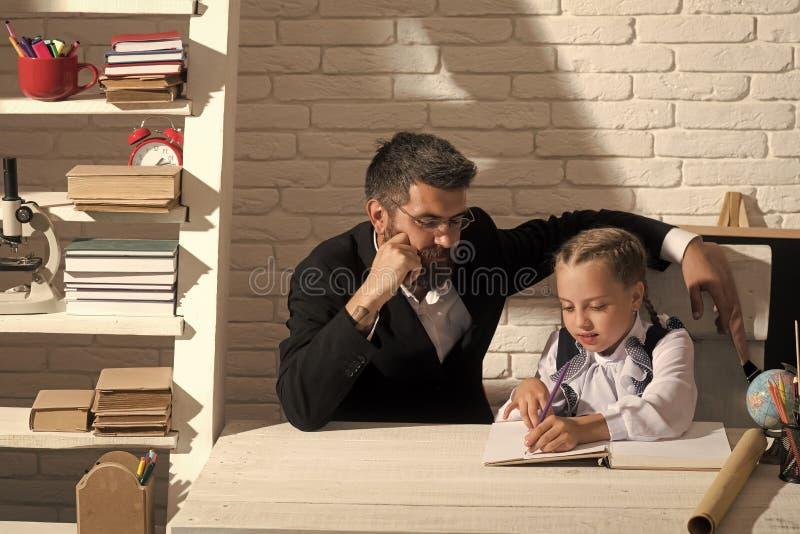 Hem- skolgång Flicka och hennes lärare i klassrum på vit tegelstenbakgrund arkivfoto