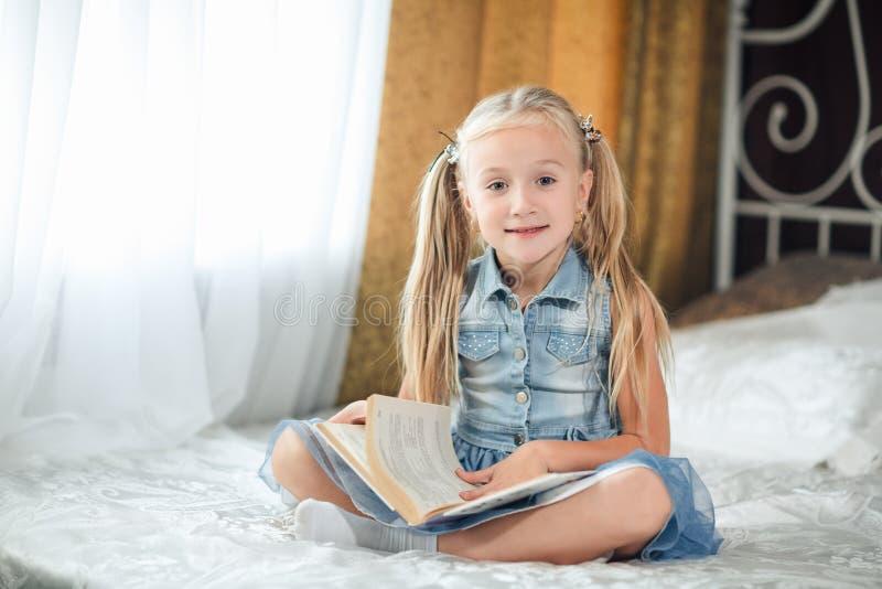 Hem- stående av lite flickan i grov bomullstvillsundress med långt blont hår som sitter i en säng med boken som ser kameran och s arkivfoto