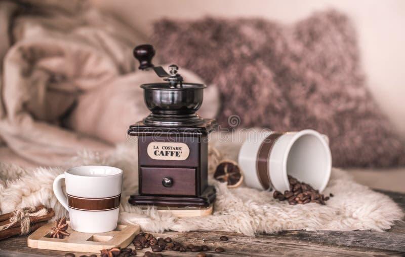Hem- stilleben i inre med en gammal kaffekvarn och bönor för en kopp kaffe, på bakgrunden av en hemtrevlig hem- dekor royaltyfri bild