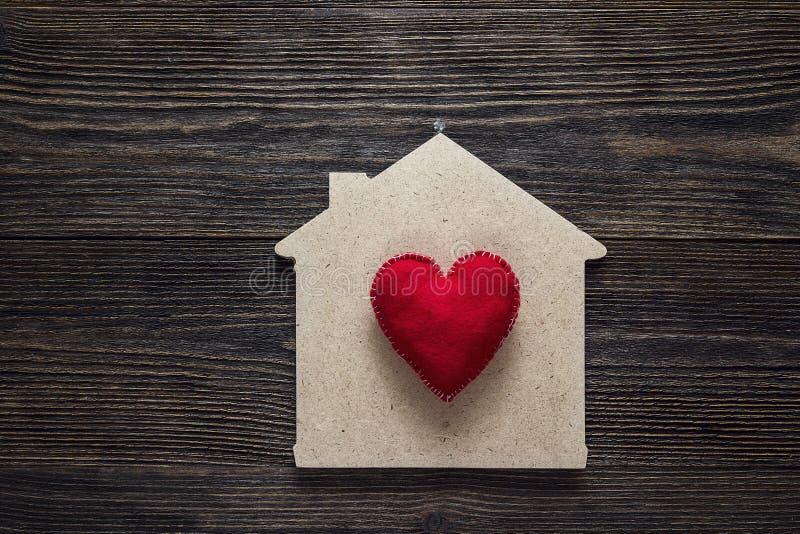 Hem- symbol med röd hjärtaform på träbakgrund fotografering för bildbyråer