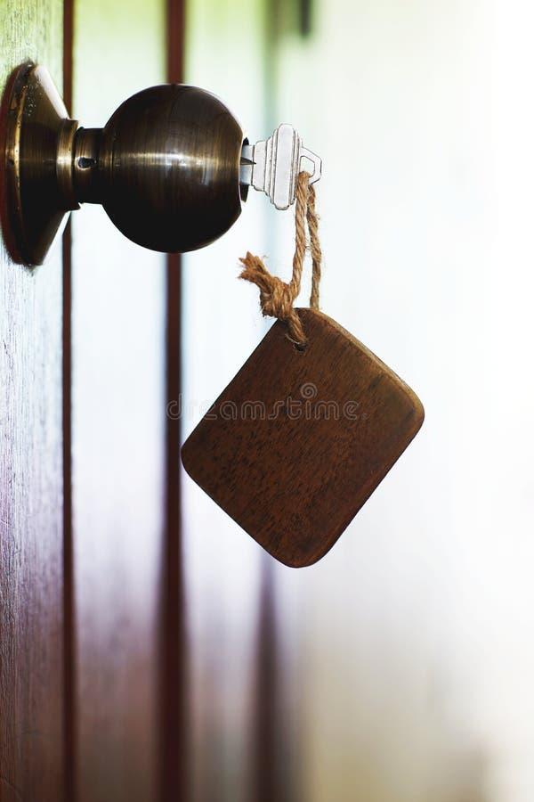 Hem- tangent med trähuskeychain i nyckelhål, egenskapsbegrepp royaltyfria bilder