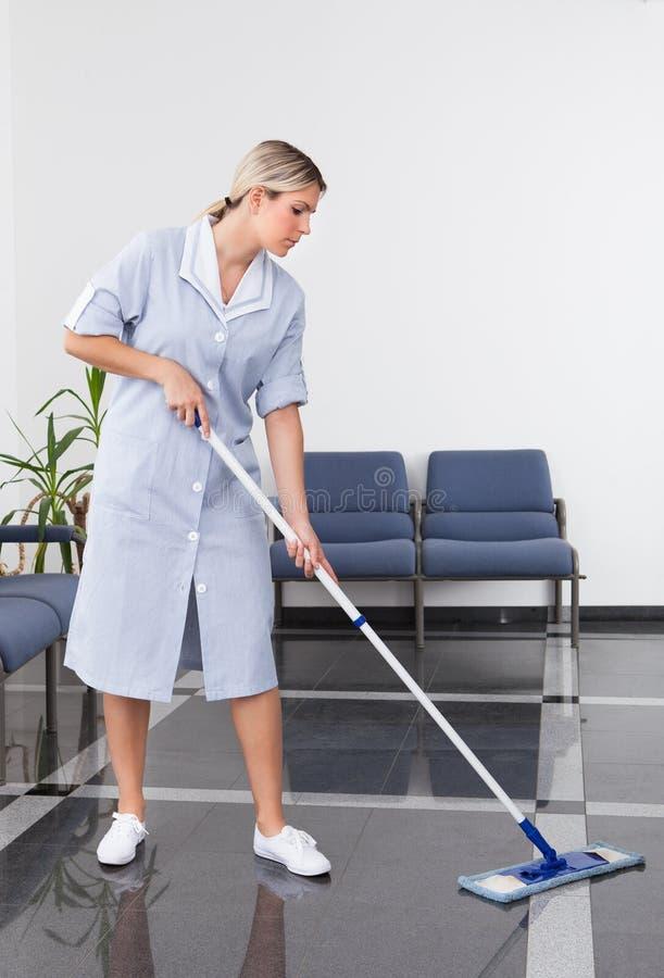 Hembiträde Cleaning The Floor royaltyfria bilder