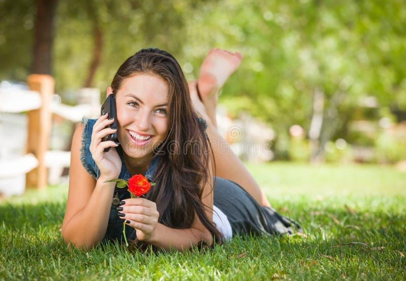 Hembra adolescente de la raza mixta feliz atractiva que habla en el tel?fono celular fotografía de archivo libre de regalías
