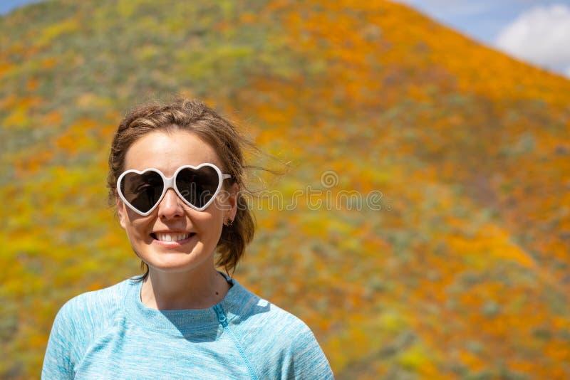 Hembra adulta feliz que presenta con las gafas de sol del corazón durante la floración estupenda de California de amapolas en Wal fotos de archivo