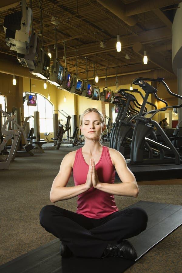 Hembra adulta que se sienta en la posición de la yoga respecto a la estera. fotografía de archivo libre de regalías