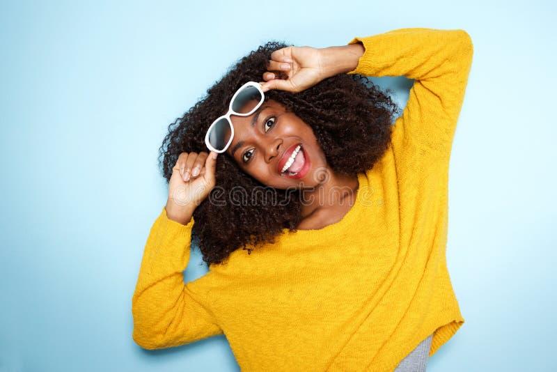 Hembra africana joven emocionada en gafas de sol en fondo azul imagen de archivo