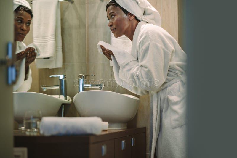 Hembra africana que limpia su cara con la toalla en cuarto de baño imagen de archivo