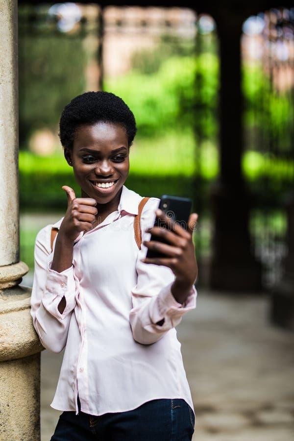 Hembra afroamericana hermosa alegre que hace el teléfono del selfie con los pulgares para arriba para publicar en redes sociales  imagen de archivo