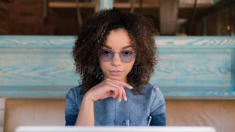 Hembra afroamericana linda con el pelo del Afro, trabajos en línea como café interior del freelancer, vidrios que llevan y vestid foto de archivo