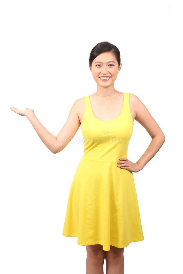 Hembra asiática en el vestido amarillo que sostiene hacia fuera la palma fotos de archivo
