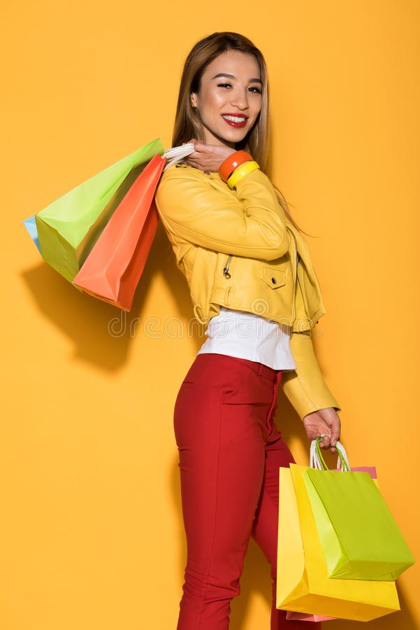 hembra asiática feliz shopaholic con las bolsas de papel en amarillo fotos de archivo