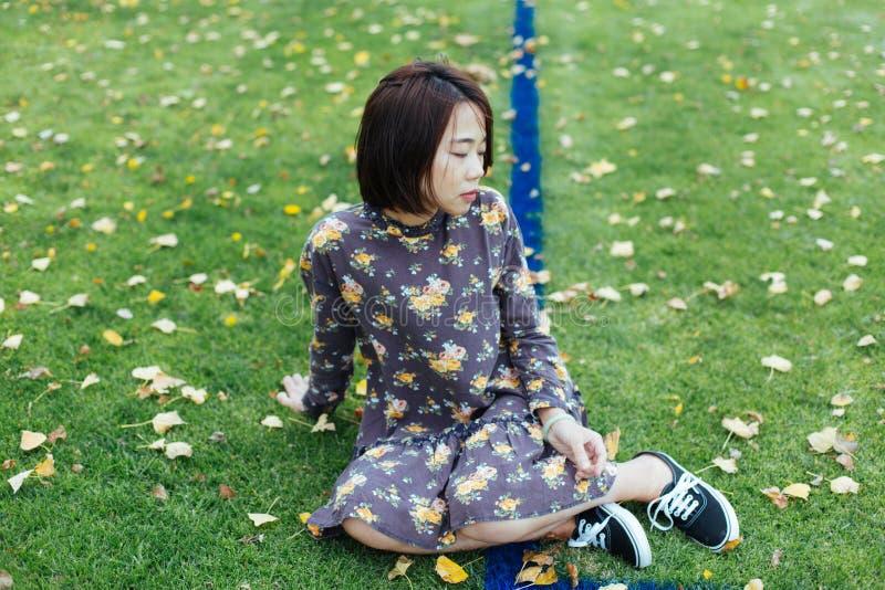 Hembra asiática que se sienta en grassground verde de la naturaleza con la chaqueta de los vaqueros imágenes de archivo libres de regalías