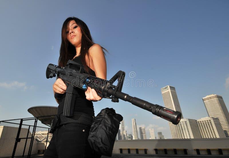 Hembra asi?tica que sostiene una ciudad de desatenci?n del rifle malo imagenes de archivo