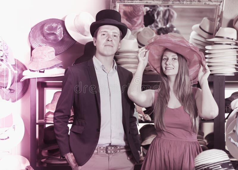 Hembra atractiva y hombre que eligen los sombreros en la tienda imágenes de archivo libres de regalías