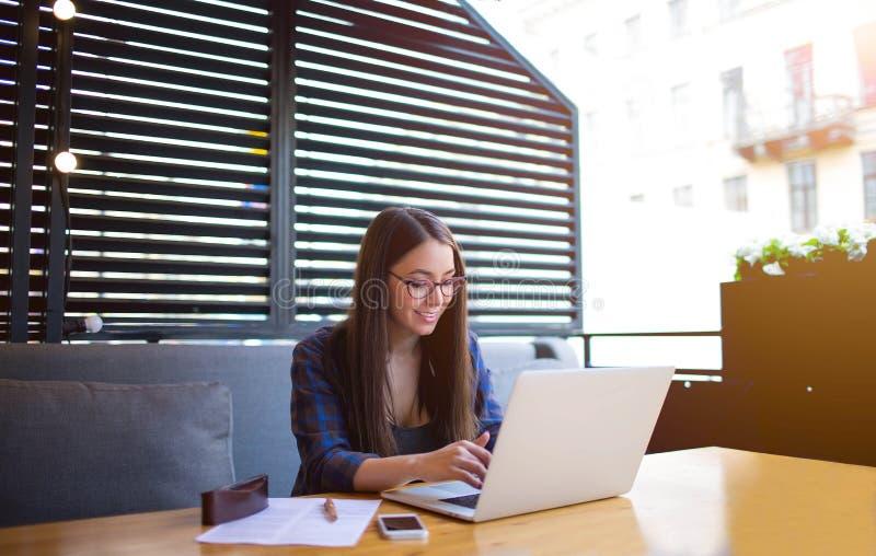 Hembra con el buen humor que tiene conversación en línea sobre el ordenador portátil durante descanso para tomar café en restaura fotografía de archivo