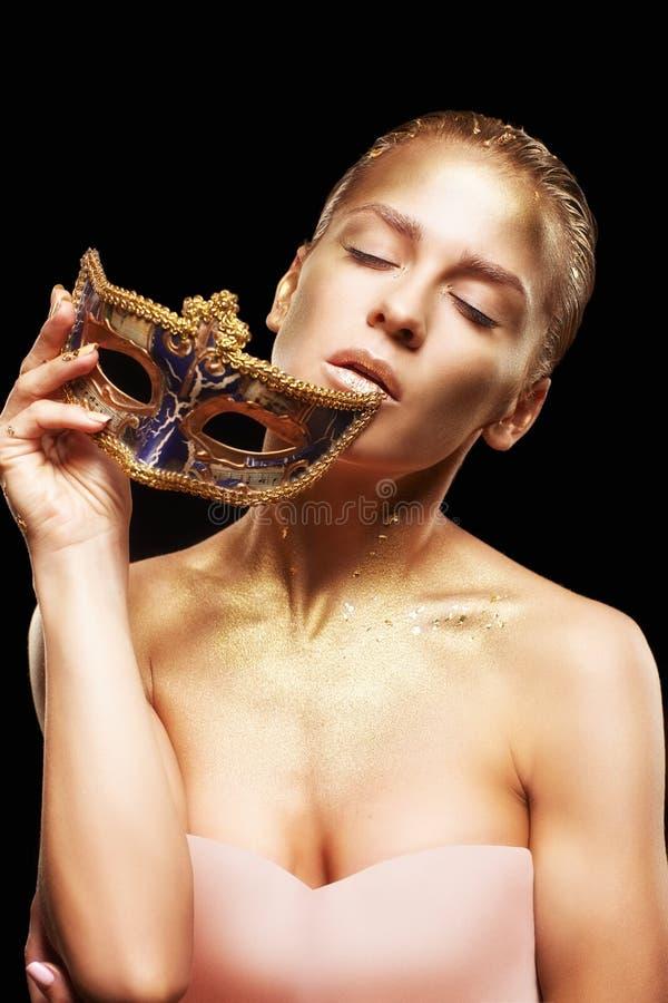 Hembra con la cara cercana disponible de la máscara venecian de la mascarada G de oro imágenes de archivo libres de regalías