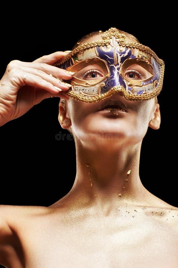 Hembra con la cara cercana disponible de la máscara venecian de la mascarada G de oro fotos de archivo libres de regalías