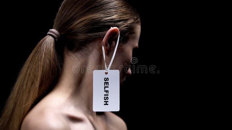 Hembra con la etiqueta egoísta en el oído contra el fondo negro, autosuficiencia fotografía de archivo