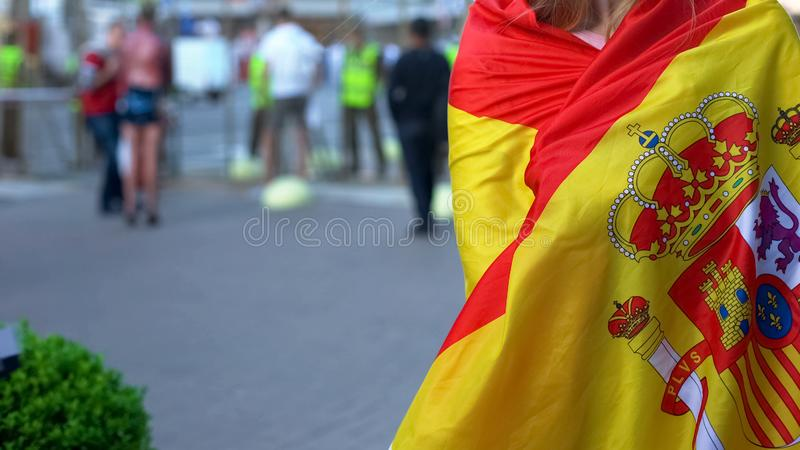 Hembra cubierta con la bandera española que se coloca en calle, patriota del país en la reunión imagen de archivo libre de regalías