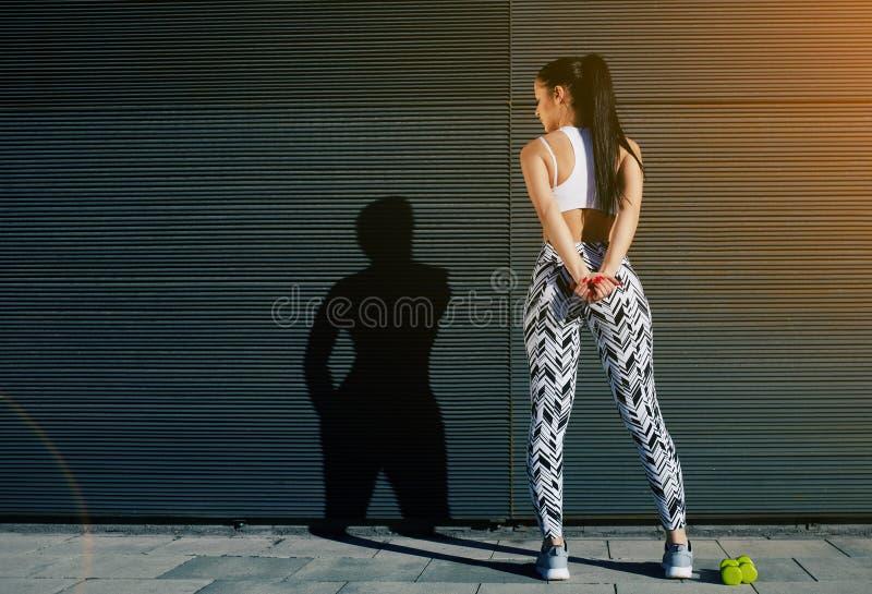 Hembra del ajuste en la ropa de deportes que descansa después de entrenar en fondo negro al aire libre fotografía de archivo