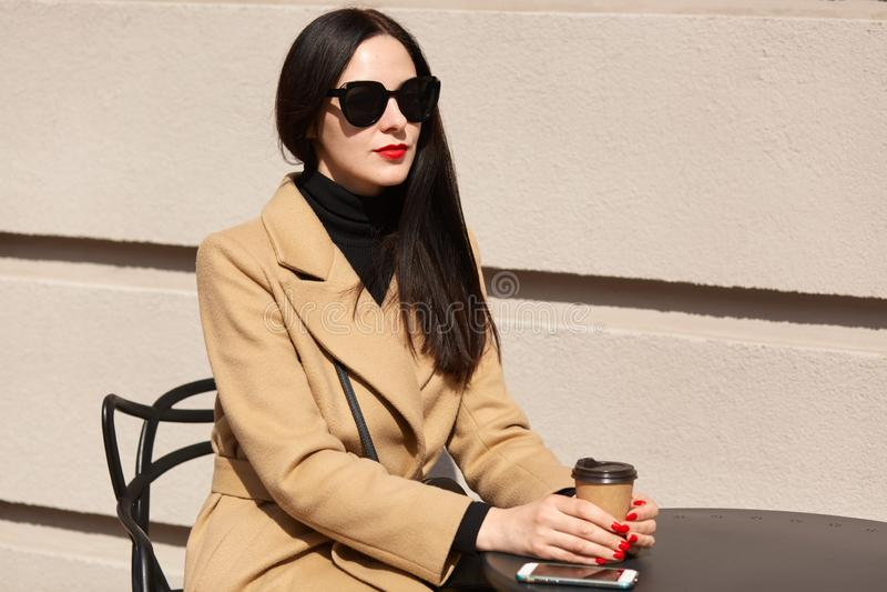 Hembra delgada morena de pelo largo con el maquillaje brillante que se sienta en la tabla al aire libre con el papercup en sus ma fotografía de archivo libre de regalías