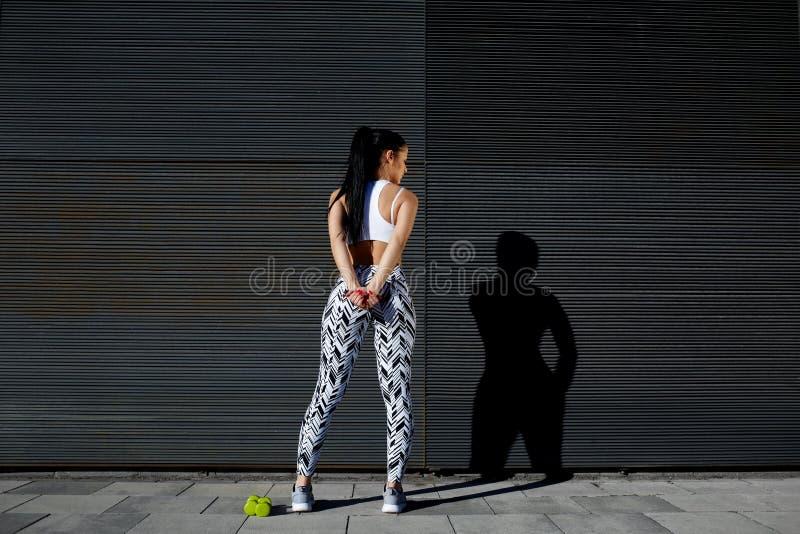 Hembra deportiva en el engranaje del entrenamiento que estira antes de ejercitar al aire libre foto de archivo