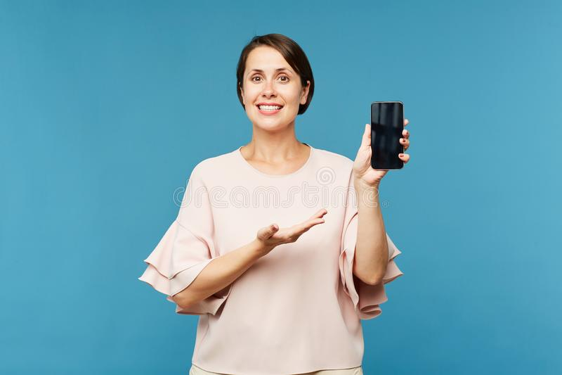 Hembra elegante joven feliz en el anuncio blanco de la demostración de la blusa en smartphone imágenes de archivo libres de regalías