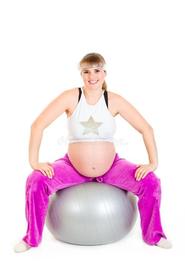 Hembra embarazada que hace ejercicios en bola de la aptitud fotos de archivo libres de regalías