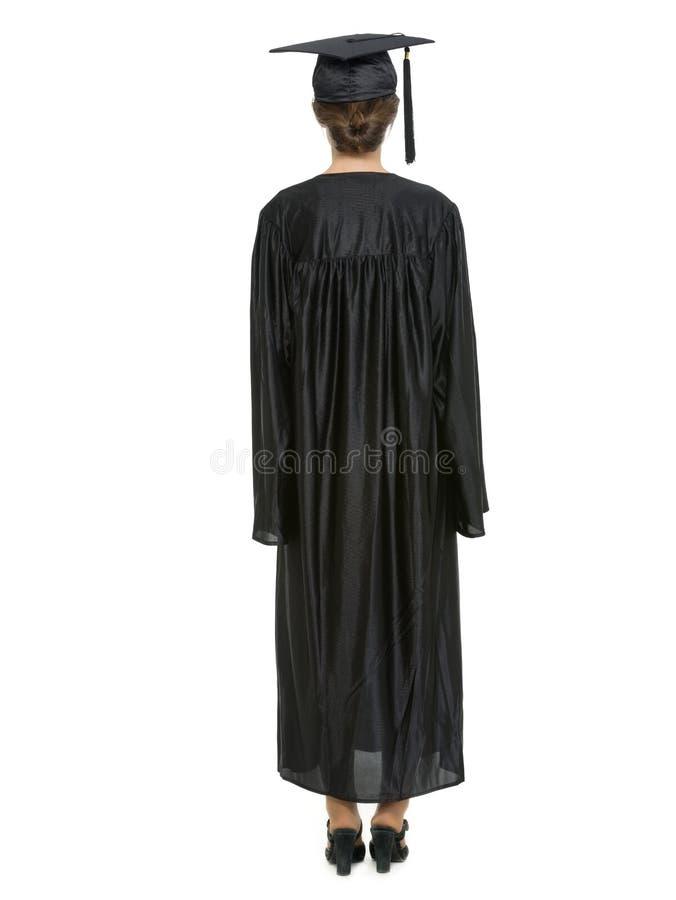 Hembra en el casquillo y el vestido de la graduación que retroceden foto de archivo libre de regalías