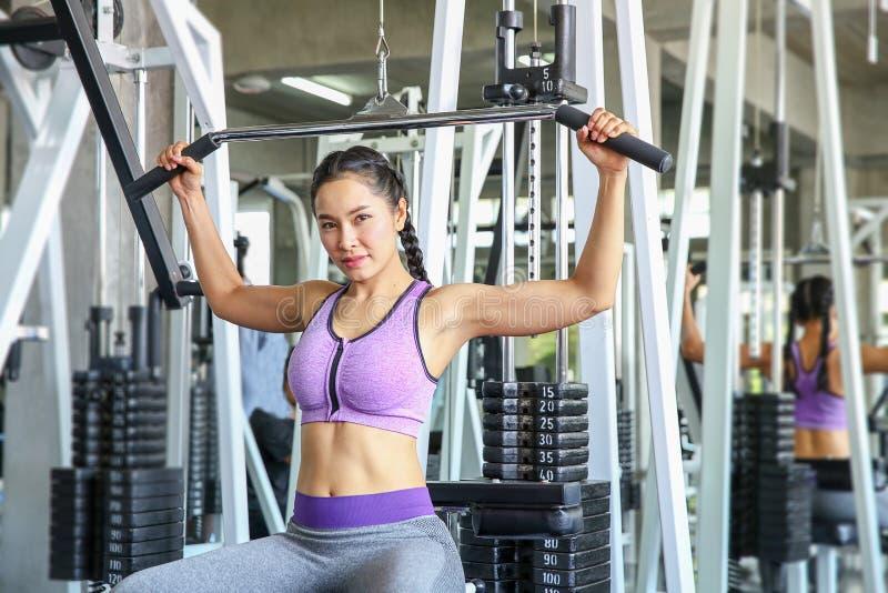 Hembra en gimnasio deporte, aptitud, levantamiento de pesas, mujer que ejercita y que dobla los músculos en la máquina en gimnasi imagen de archivo libre de regalías