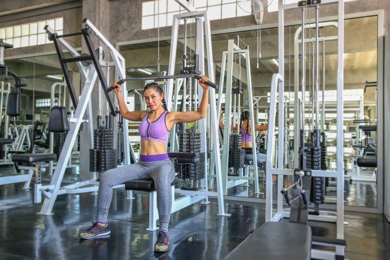 Hembra en gimnasio deporte, aptitud, levantamiento de pesas, mujer que ejercita y que dobla los músculos en la máquina en gimnasi imágenes de archivo libres de regalías