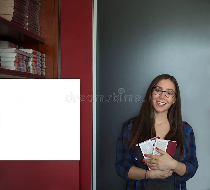 Hembra encantadora con la literatura que presenta para la cámara durante el aprendizaje en universidad imagen de archivo libre de regalías